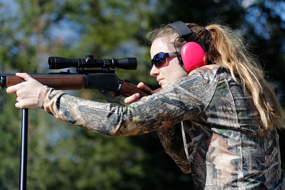 A woman aiming a rifle.