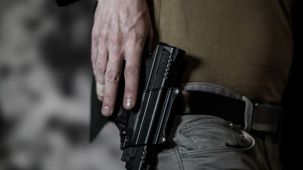 Man reaching for a pistol on his belt