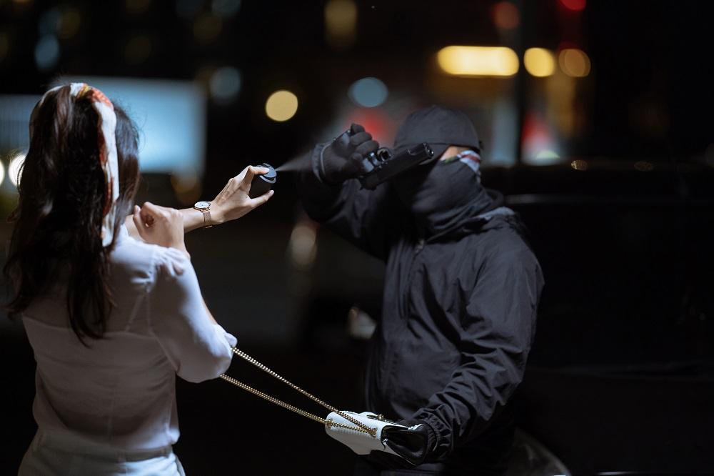 woman in self defense using pepper spray