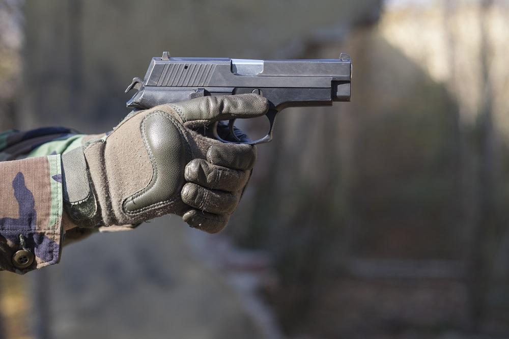 gun and camouflage gloves